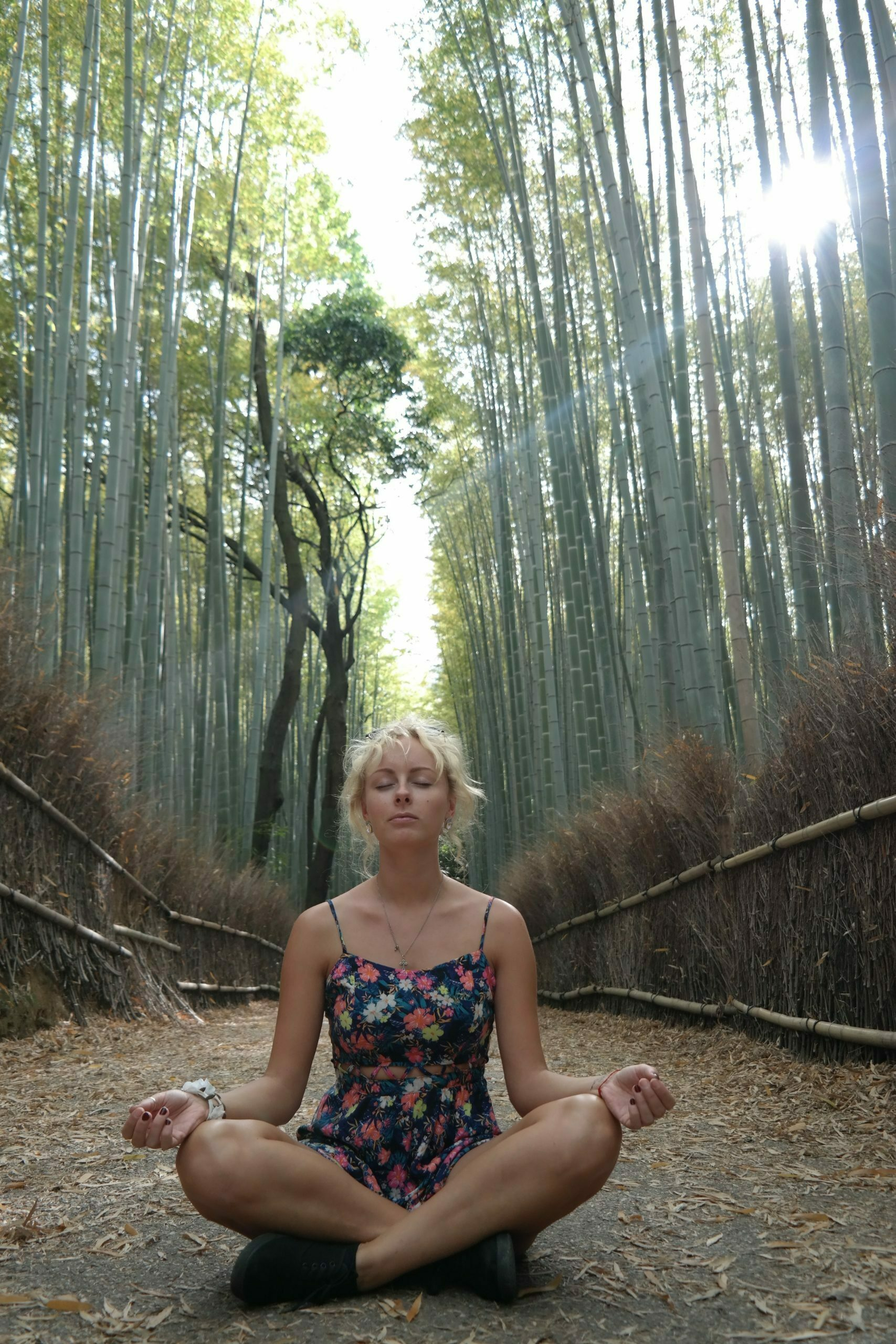 young blond girl meditating in bamboo forest