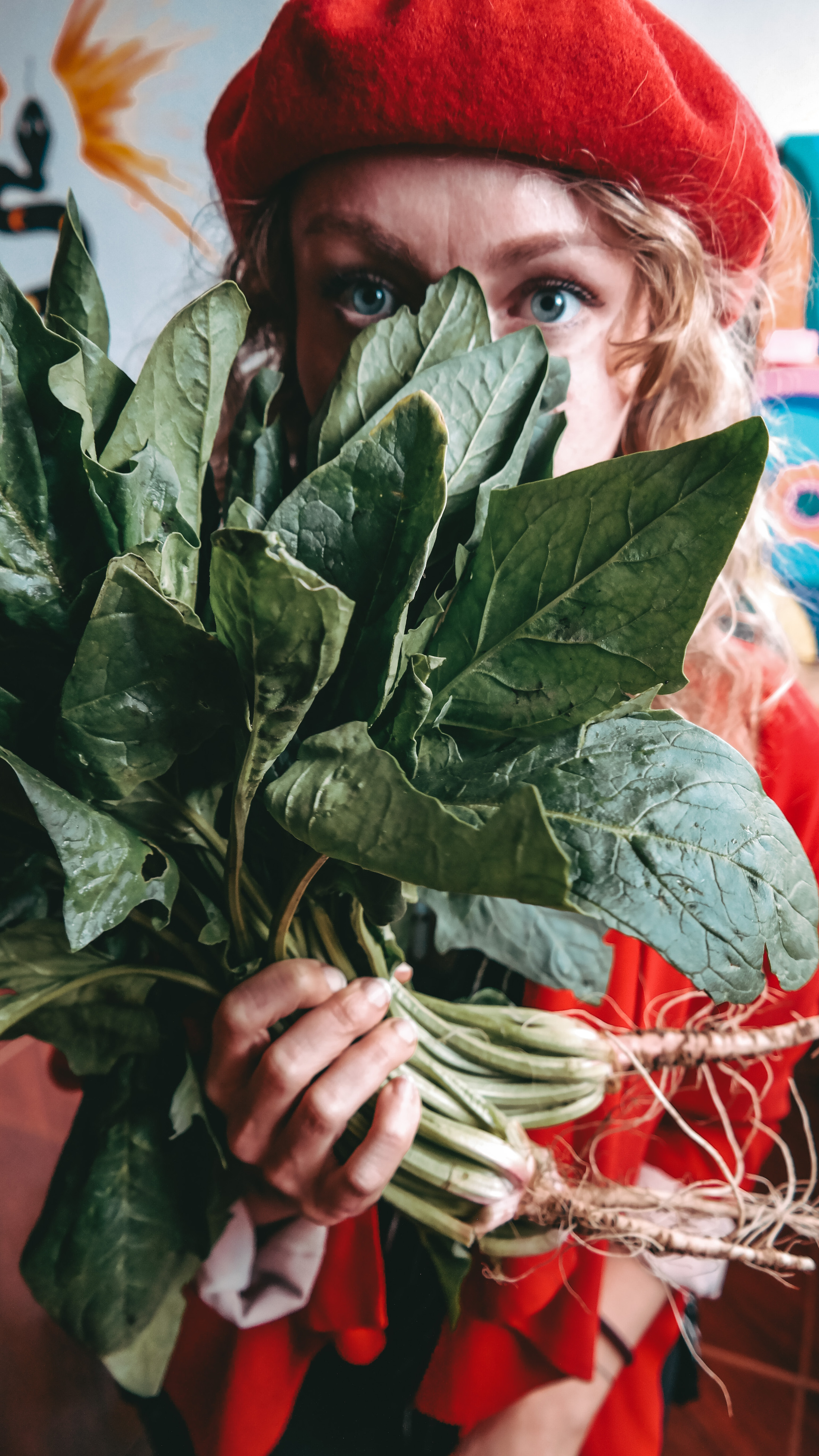 woman in red holding a spinach