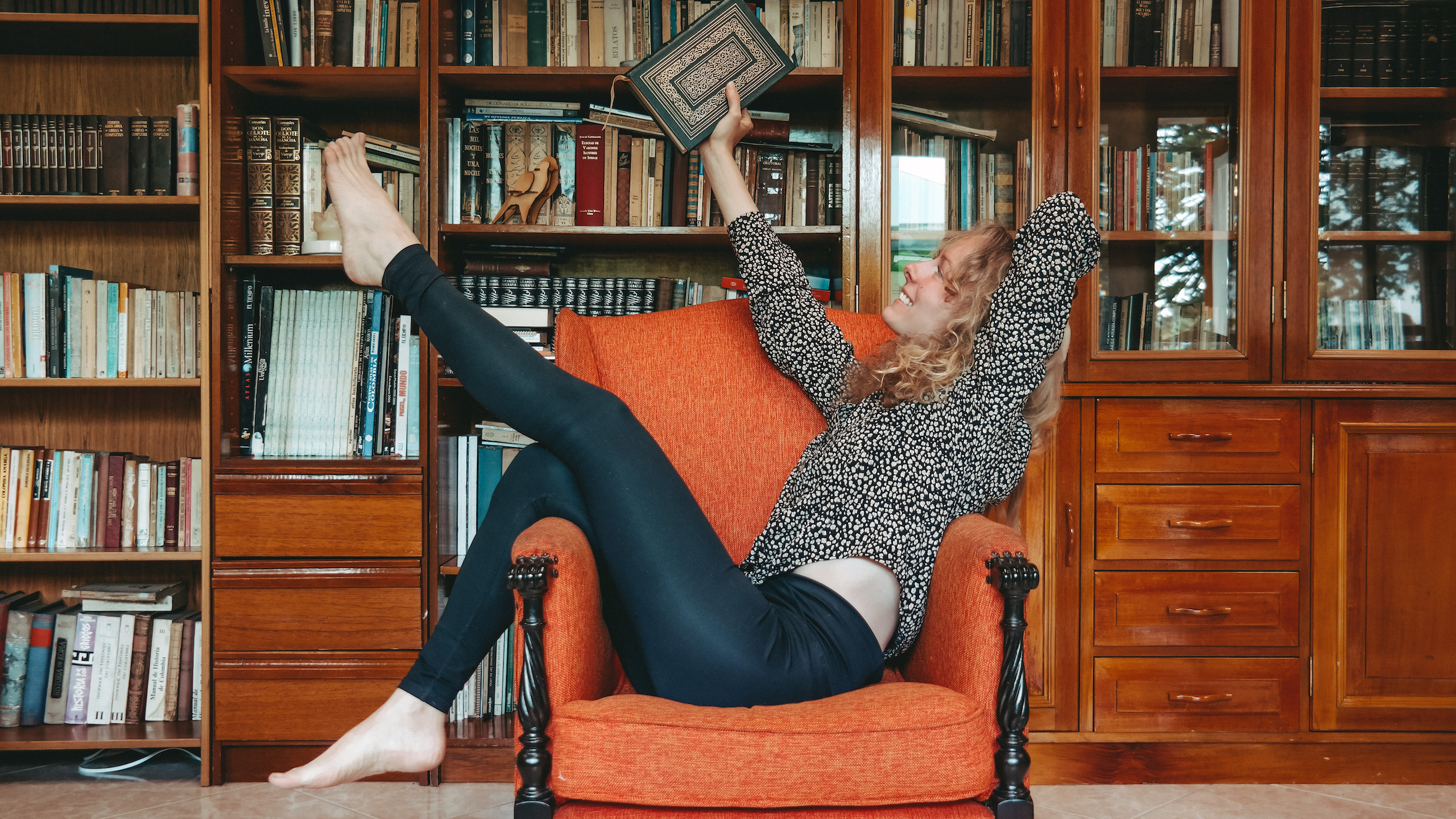 woman on an orange chair in a library holding a book