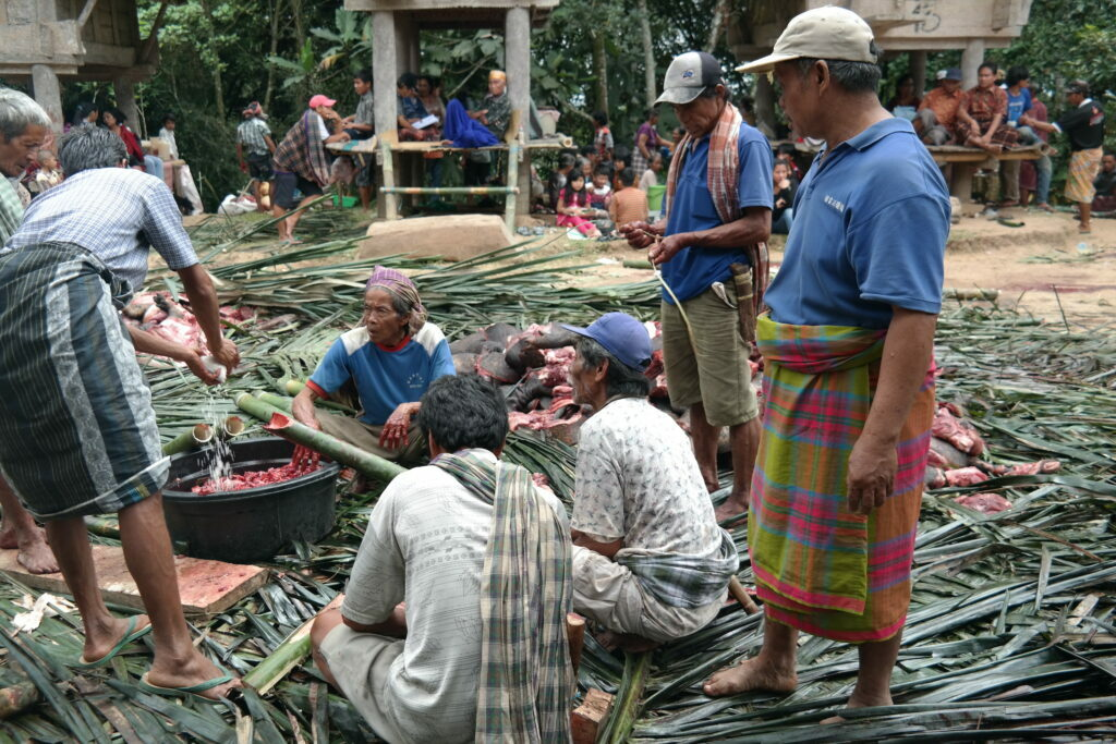 indigenous men from indonesia cooking