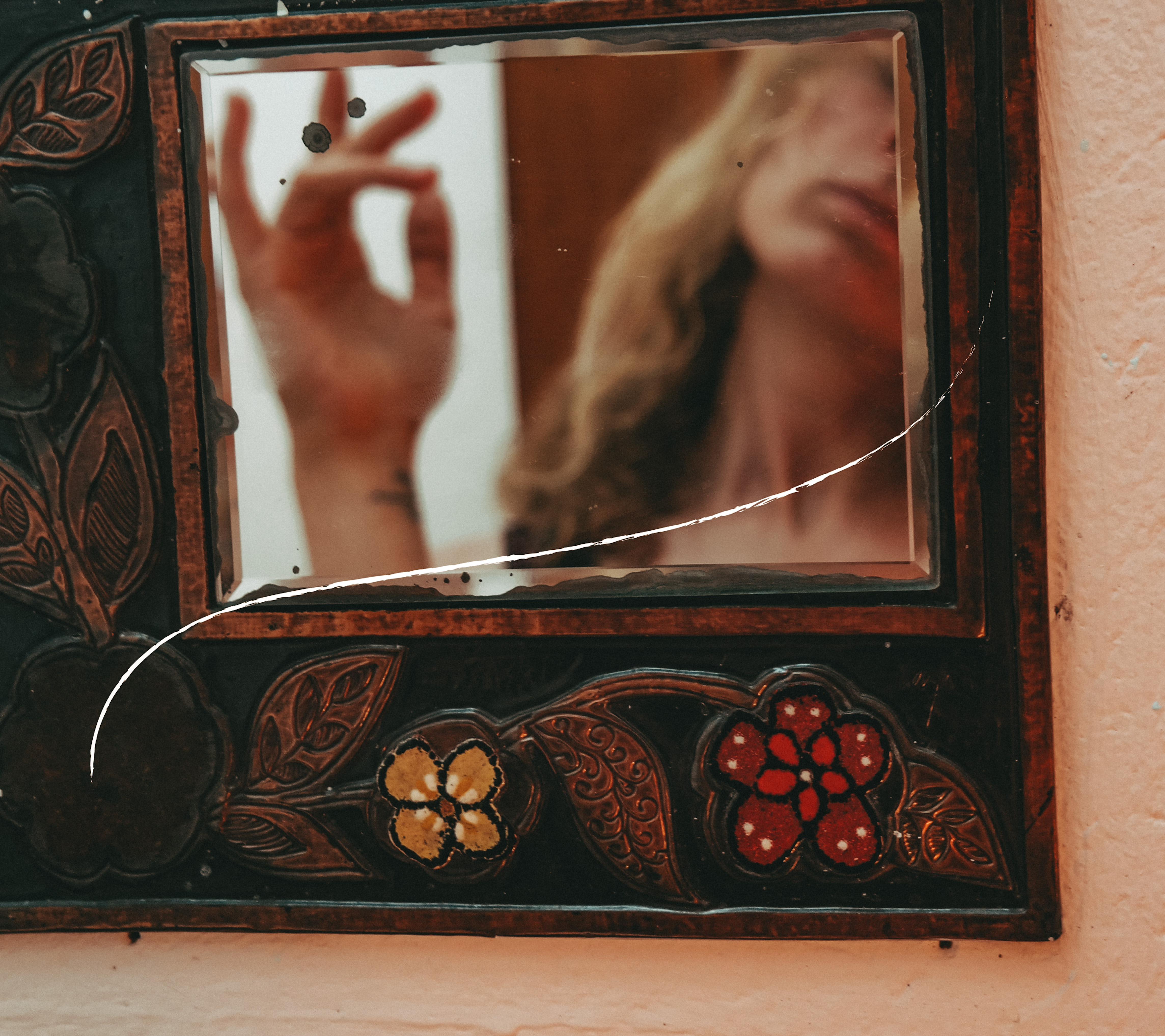 hand and face of a woman in a mirror