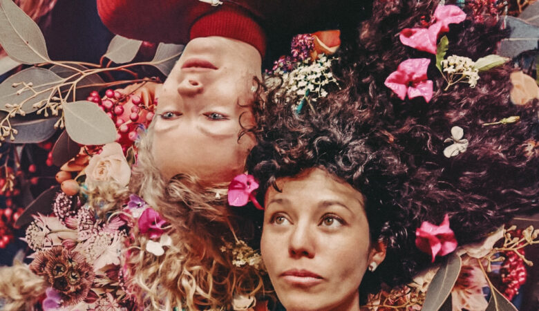 two women laying on the ground thinking about ageing, surrounded by beautiful flowers