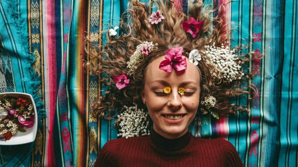 young smiling woman laying on the ground covered with flowers